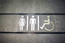 Sign Of Public Toilets WC On Wall Outdoors. For Female, Male And Disabled People