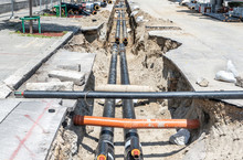 District Heating Pipeline Reparation And Reconstruction Site Parallel With The Street With Construction Site Safety Net Fence And Insulated Pipes For Hot Water In The Trench Before Winter Season Come
