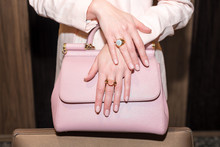 Woman Hands With Manicure And Luxury Jewelry Rings. Close Up Of Trendy Leather Pink Bag With Female Hands Showing Fashion Jewelry At Camera. Concept Of Manicure And Fashion.