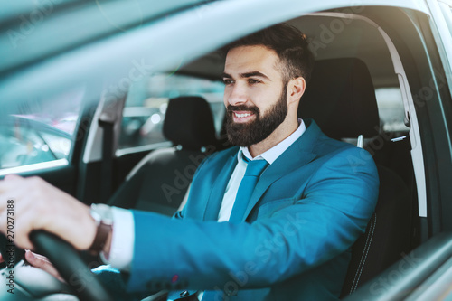 Young attractive prosperous Caucasian businessman in blue suit driving his car Poster Mural XXL
