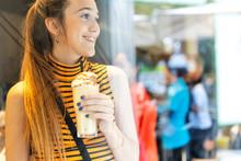 Spain, Smiling Teenage Girl Enjoying A Milk Shake
