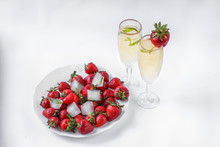 Two Glasses Of Champagne And A Plate Of Strawberries