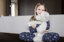 Portrait Of Smiling Little Girl Wearing Pajamas With Floral Design Holding White Teddy Bear