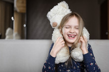 Smiling Girl Holding White Teddy Bear At Home