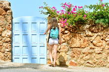 Girl With Backpack Returns From A Walk And Opens Blue Vintage Door In Mediterranean Style.