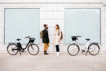 Smiling Couple With E Bikes Standing Near Wall