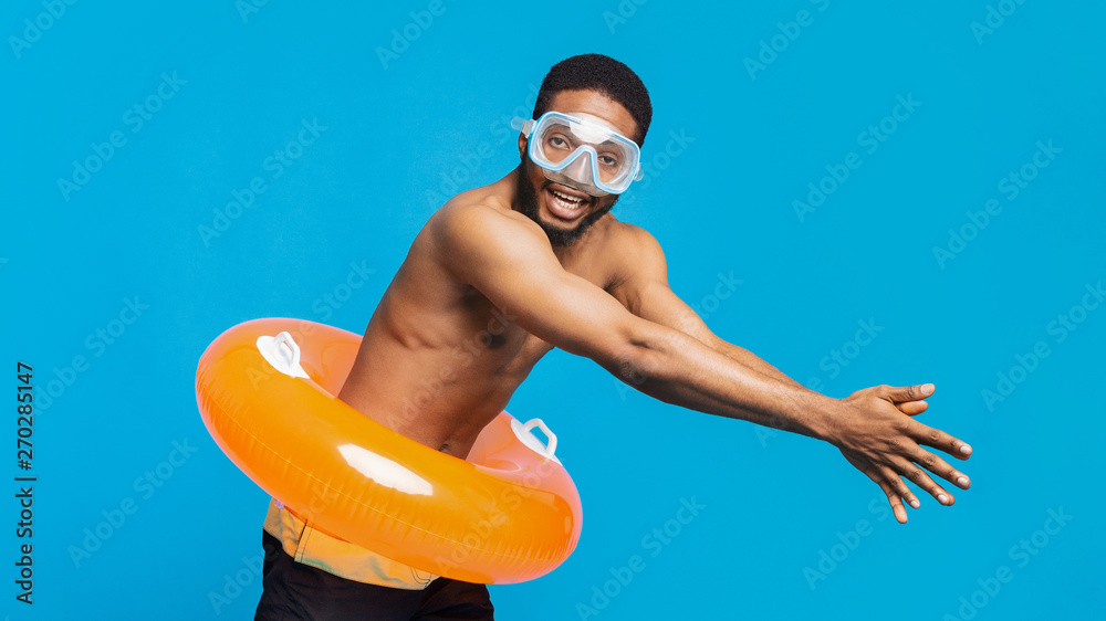 Fototapeta Black guy in scuba mask and inflatable ring diving on blue