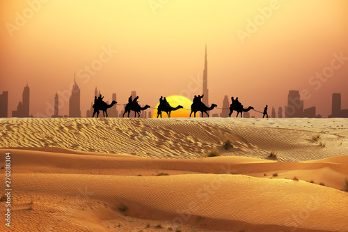 Fotobehang Dubai Dubai skyline at horizon with camel ride caravan silhouette in desert
