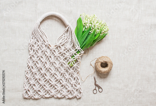 Poster Muguet de mai Handmade macrame bag on the linen background, ECO friendly. Embroidery. Modern summer concept. Lily of the valley bouquet