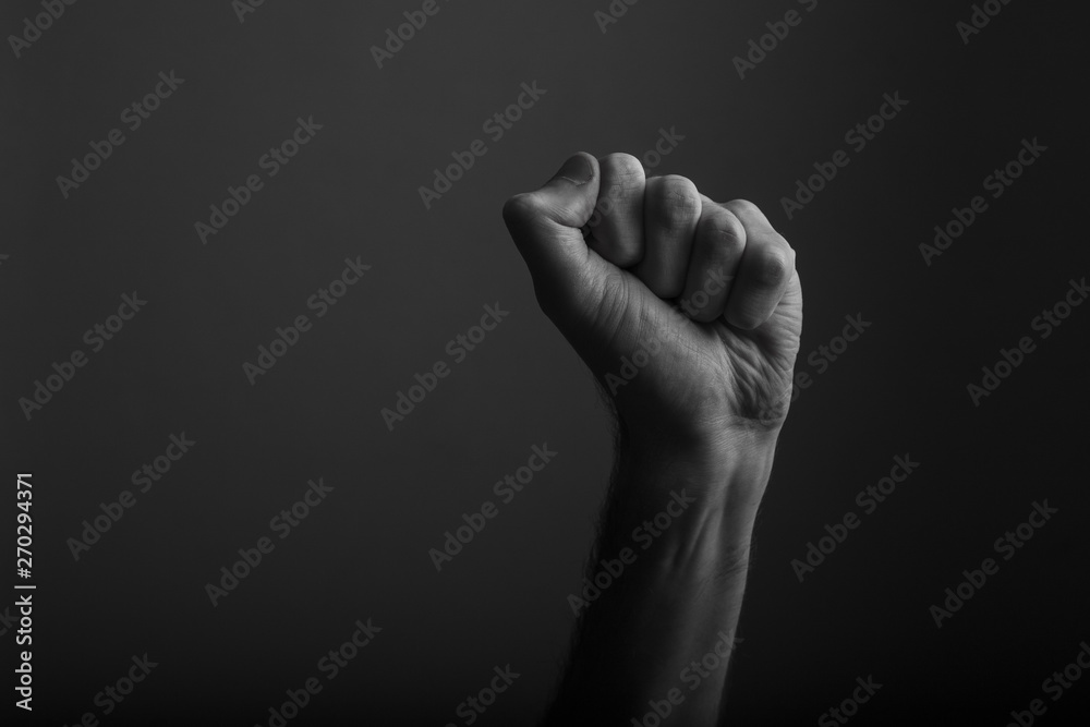 Fototapety, obrazy: Raised clenched fist against a dark background, power, protest concept