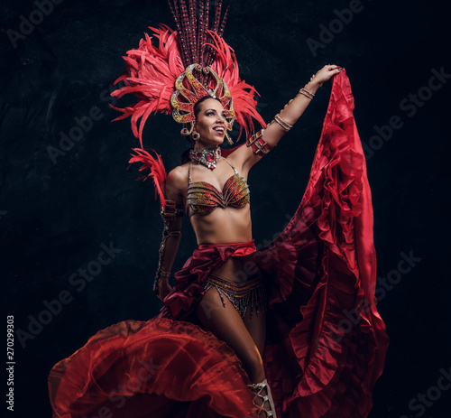 Foto Talented joyful can can dancer in red feather costume is posing at small dark studio