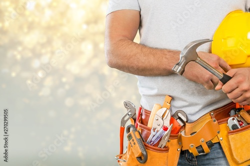 Fotografia  Worker with a tool belt. Isolated over white background.