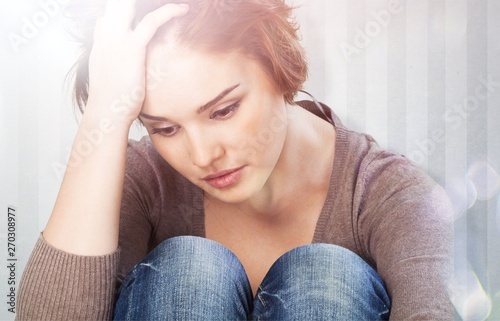 Worried woman sitting holding knees with arm on background
