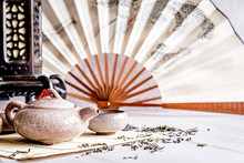 Asian Teapot With Teacups On Bamboo Tablamat Decorated With Chinese Fan, Lantern And Scattered Green Tea On White Marble Background
