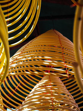 Multiple Large Yellow Incense Coils Hanging In Stacks From The Ceiling In A Chinese Temple