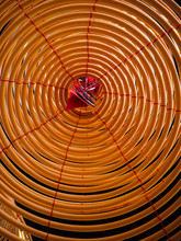 Low Angle View On The Inside Of A Large Yellow Incense Coil Hanging From The Ceiling In A Chinese Temple