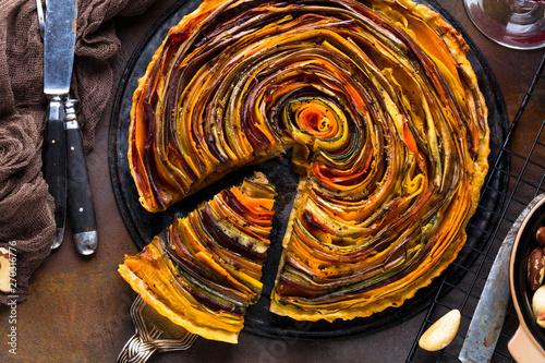 Fotobehang Spiraal Spiral Gemüse Tarte auf bunt dekoriertem tisch.