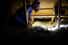 Working In A Dark And Dusty Attic With Insulation