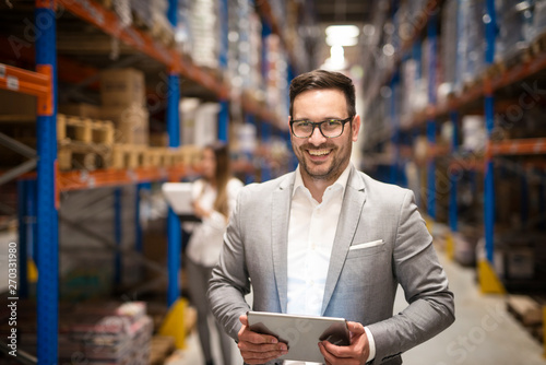 Valokuva  Portrait of successful middle aged caucasian manager businessman holding tablet computer in large warehouse organizing distribution
