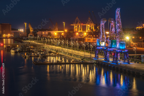 obraz dibond Illuminated old port cranes on a boulevard in Szczecin City at night