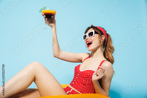 Photo sur Aluminium Kiev Young pin up pretty summer girl in swimwear posing isolated over blue background in inflatable ring drinking cocktail.