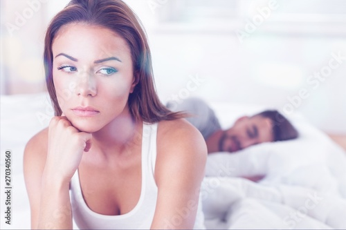 Photographie Dissatisfied beautiful young woman in bed with sad expression on her face, sex problems in long relationship or marriage while man sleeping