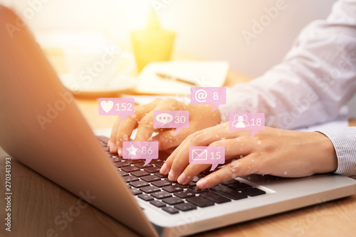 people using notebook computer laptop for social media interactions with notification icons from friend in social network with like, message, email, mention and star above smartphone screen. internet