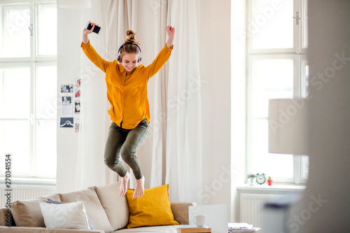 Canvas Print A young female student with headphones jumping on sofa when studying