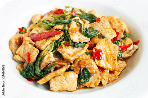 Photo Stir-fried hot and spicy pork with basil on white