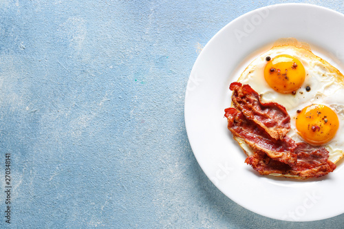 Plate with tasty fried eggs and bacon on color background Fototapeta