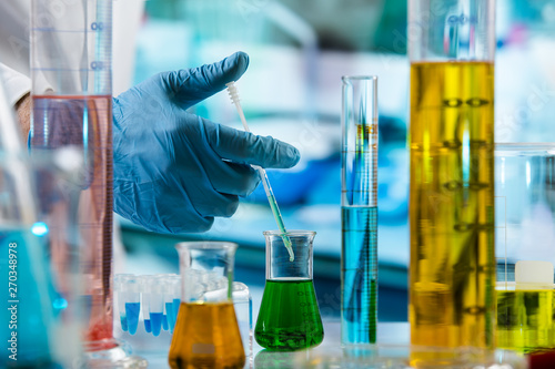 Fotografia  hand of researcher with pipette measuring sample in beaker of liquids in the che