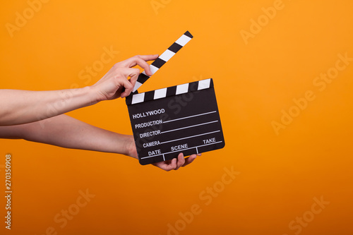 Photo Woman holding professional film slate, movie clapper board in studio over yellow
