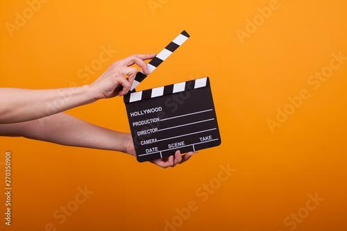 Papel de parede Woman holding professional film slate, movie clapper board in studio over yellow