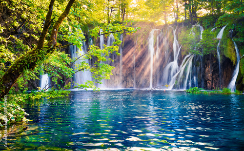 Stickers pour portes Rivière de la forêt Last sunlight lights up the pure water waterfall on Plitvice National Park. Colorful spring scene of green forest with blue lake. Great countryside view of Croatia, Europe.