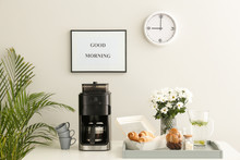 Modern Coffee Machine, Sweets And Flowers On Kitchen Table