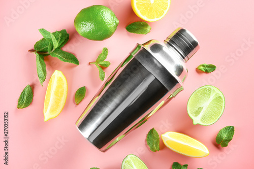 Photo Fresh lime, lemon, shaker and mint leaves on color background