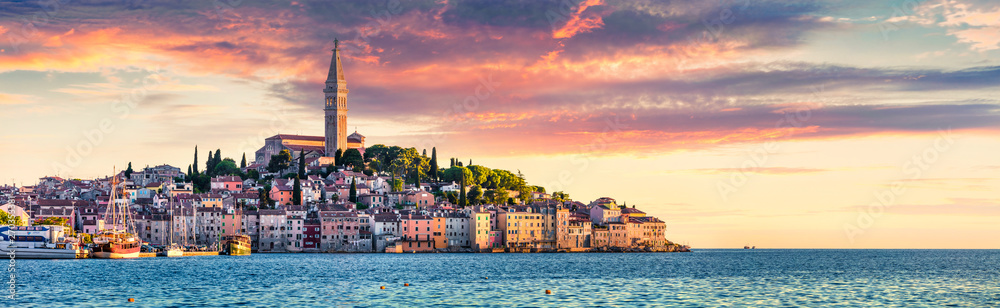 Fototapeta Great spring sunset of Rovinj town, Croatian fishing port on the west coast of the Istrian peninsula. Colorful evening seascape of Adriatic Sea. Traveling concept background.