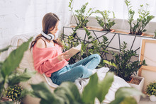 Selective Focus Of Young Woman Reading Book While Sitting With Crossed Legs Surrounded By Lush Plants At Home