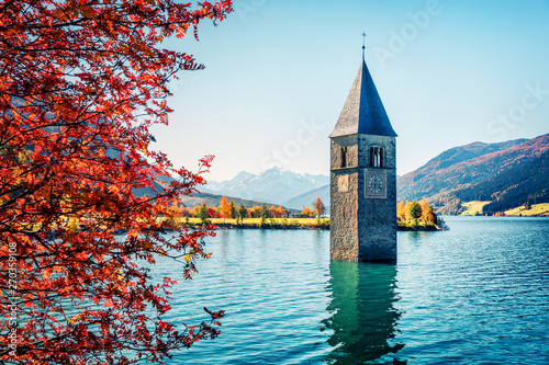 Foto  Fantastic autumn view of Tower of sunken church in Resia lake