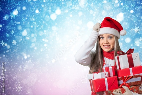 Photo sur Toile Les Textures Young girl with christmas gifts on light blurred background