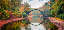 Unbelievable Morning Scene Of Azalea And Rhododendron Park Kromlau, Germany, Europe. Great Autumn Panorama Of Rakotz Bridge (Rakotzbrucke, Devil's Bridge). Traveling Concept Background.