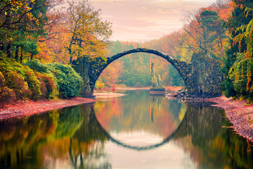 Panel Szklany Do Spa Impressive sunset in Azalea and Rhododendron Park Kromlau, Germany, Europe. Picturesque autumn view of Rakotz Bridge (Rakotzbrucke, Devil's Bridge). Traveling concept background.