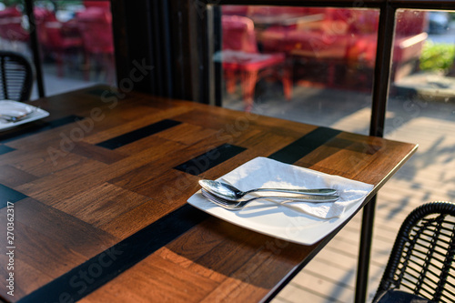 Foto  White dish with fork and spoon on wooden dining table