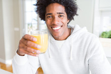 African American Man Holding And Drinking Glass Of Orange Juice With A Happy Face Standing And Smiling With A Confident Smile Showing Teeth