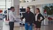 Salesman transmitting keys to young couple in car dealership