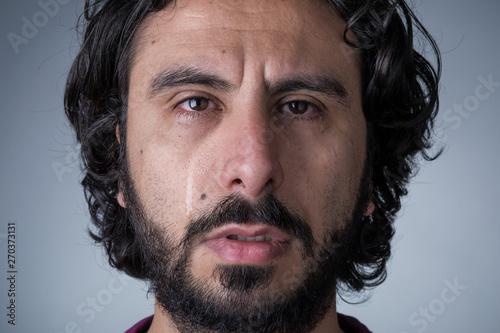 Fotomural  Man with Beard and Long Hair Crying Looking at Camera