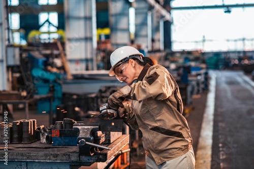 Fotografia Female industrial worker in protective work wear grinding metal in factory workshop