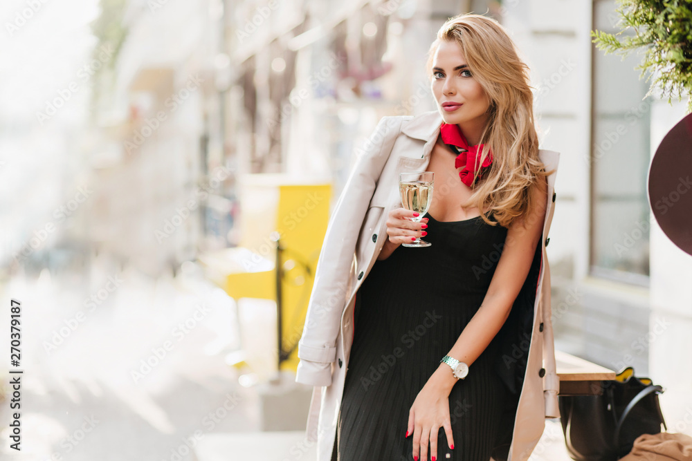 Fototapeta Curly blonde woman in black pleated dress celebrating something with champagne. Outdoor portrait of glad fair-haired girl holding glass of wine on blur background.