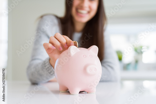 Fotomural  Young woman smiling putting a coin inside piggy bank as savings for investment
