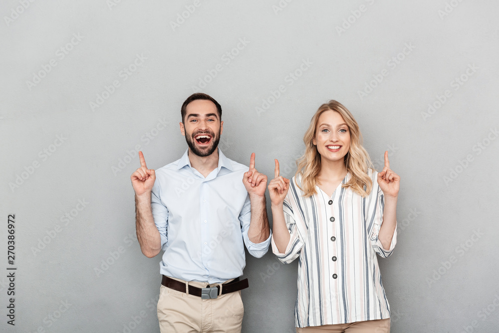 Fototapeta Photo of nice couple in casual clothing smiling while pointing fingers at copyspace